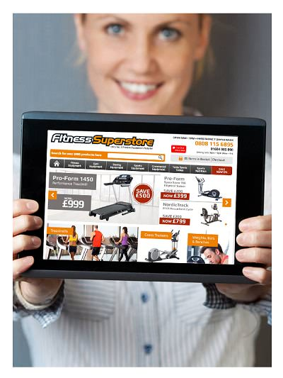 Woman holding up iPad showing Fitness Superstore website